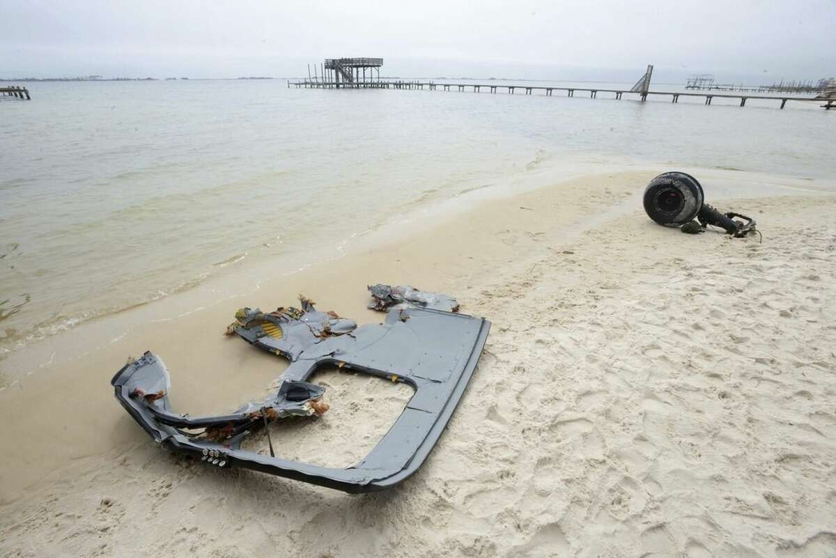 A wheel and pieces of fuselage from an Army Black Hawk helicopter sit along the shoreline of Santa Rosa Sound near Navarre, Fla. on Wednesday, March 11, 2015. Search and rescue crews battled heavy fog Wednesday as they combed the water looking for survivors from the aircraft, which went down in this area Tuesday evening with 11 service members aboard. (AP Photo/Northwest Florida Daily News, Devon Ravine)