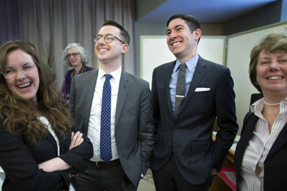 Thomas Rimbey Ogletree, center left, and Nicholas Haddad, center right, smile following a news conference announcing that a case against Ogletree's father, Rev. Thomas Ogletree, for breaking church law by officiating their same-sex marriage had been dropped, Monday, March 10, 2014, in White Plains, N.Y. Bishop Martin McLee, who announced the decision, called on church officials to stop prosecuting other pastors for marrying same-sex couples. McLee, who leads the church's New York district said he would cease church trials over the issue in his district and would organize a broad discussion about the church's internal divisions over gay relationships. (AP Photo/John Minchillo)