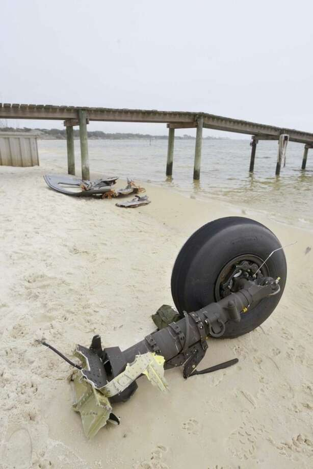 A wheel and pieces of fuselage from an Army Black Hawk helicopter sit along the shoreline of Santa Rosa Sound near Navarre, Fla. on Wednesday, March 11, 2015. Search and rescue crews battled heavy fog Wednesday as they combed the water looking for survivors from the aircraft, which went down in this area Tuesday evening with 11 service members aboard. March 11, 2015. (AP Photo/Northwest Florida Daily News, Devon Ravine)