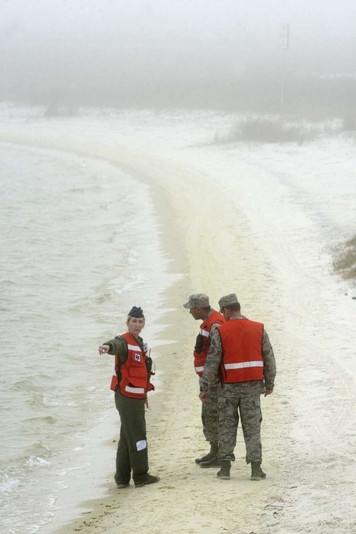 Unidentified military personnel search the shoreline of Santa Rosa Island near Navarre, Fla. Wednesday, March 11, 2015 near the site where an Army Black Hawk helicopter went down Tuesday evening with 11 service members aboard. (AP Photo/Northwest Florida Daily News, Devon Ravine)