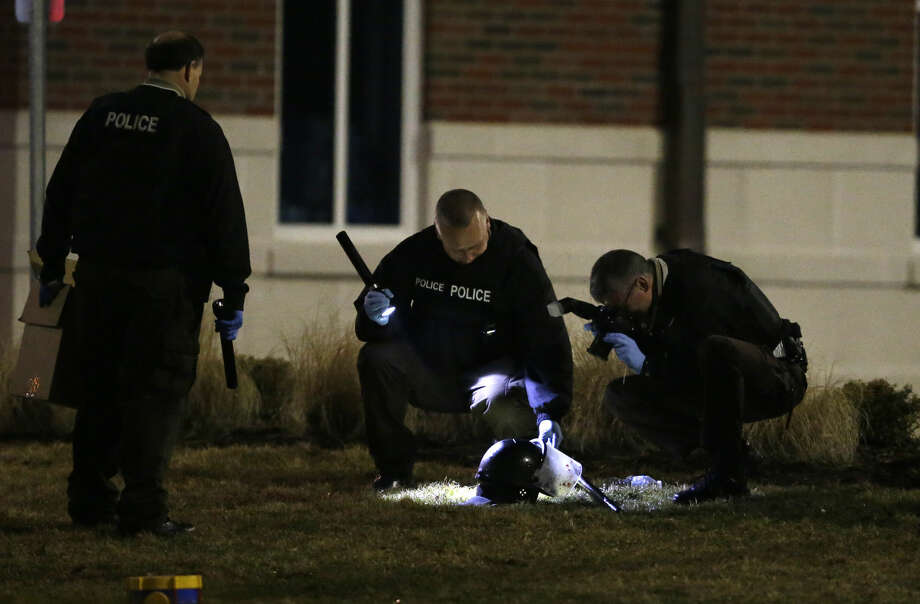 Police shine a light on and photograph a helmet as they investigate the scene where two police officers were shot outside the Ferguson Police Department Thursday, March 12, 2015, in Ferguson, Mo. (AP Photo/Jeff Roberson)