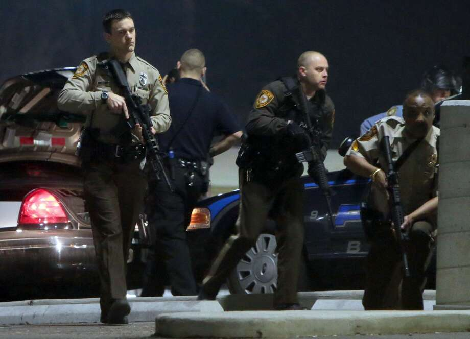 Police mobilize in the parking lot of the Ferguson Police Station after two police officers were shot while standing guard in front of the Ferguson Police Station on Thursday, March 12, 2015. (AP Photo/St. Louis Post-Dispatch, Laurie Skrivan)