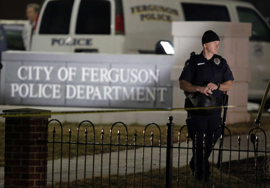 Police stand watch outside the Ferguson Police Department where two police officers were shot Thursday, March 12, 2015, in Ferguson, Mo. (AP Photo/Jeff Roberson)