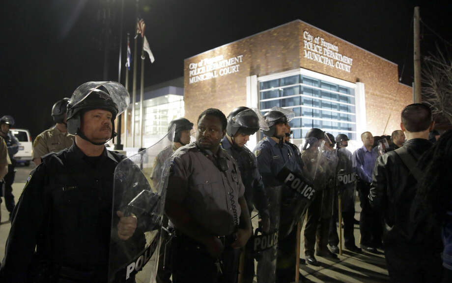 Police form a line outside the Ferguson Police Department as people demonstrate nearby Wednesday, March 11, 2015, in Ferguson, Mo. Earlier in the day, the resignation of Ferguson police chief Thomas Jackson was announced in the wake of a scathing Justice Department report prompted by the fatal shooting of an unarmed black 18-year-old by a white police officer. (AP Photo/Jeff Roberson)