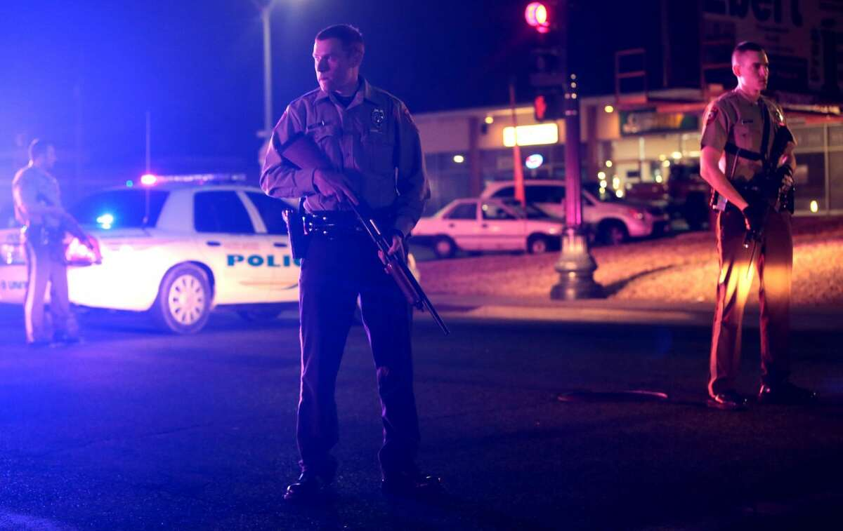 Police guard the corner off Adams Street and South Florissant Rd after two officers were shot while standing guard in front of the Ferguson Police Station on Thursday, March 12, 2015. (AP Photo/St. Louis Post-Dispatch, Laurie Skrivan)
