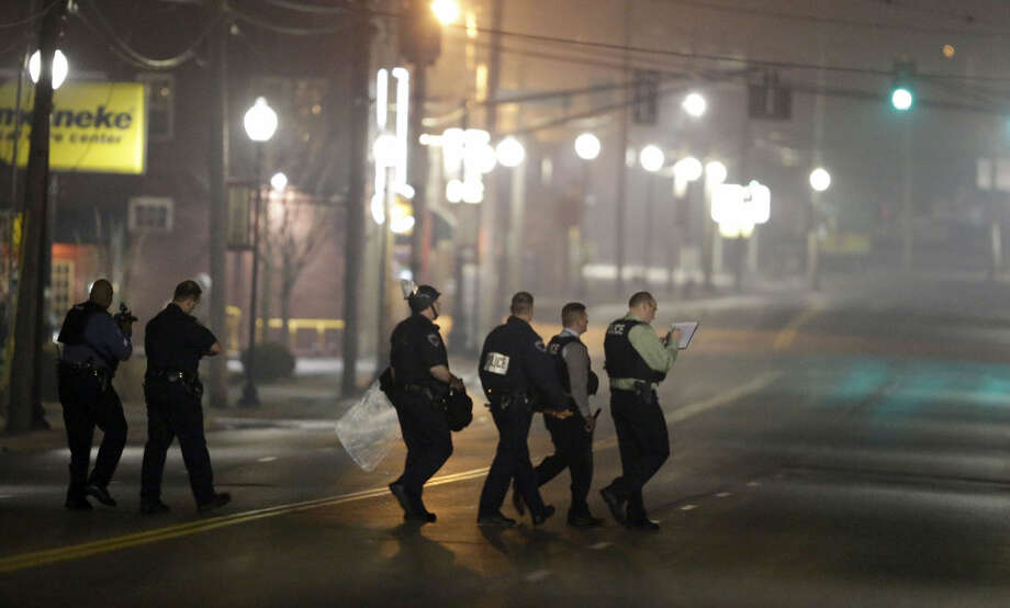 Police canvass the area as they investigate the scene where two police officers were shot outside the Ferguson Police Department Thursday, March 12, 2015, in Ferguson, Mo. (AP Photo/Jeff Roberson)