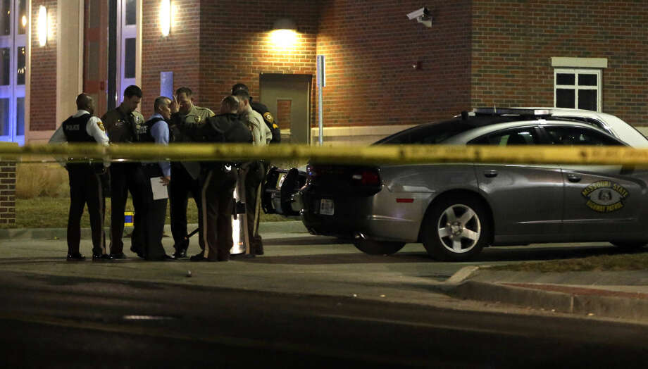 Police gather outside the Ferguson Police Department Thursday, March 12, 2015, after two police officers were shot according to witnesses in Ferguson, Mo. (AP Photo/Jeff Roberson)