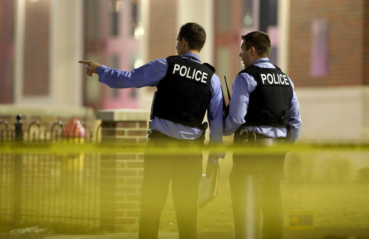 Police investigate the scene where two police officers were shot outside the Ferguson Police Department Thursday, March 12, 2015, in Ferguson, Mo. (AP Photo/Jeff Roberson)