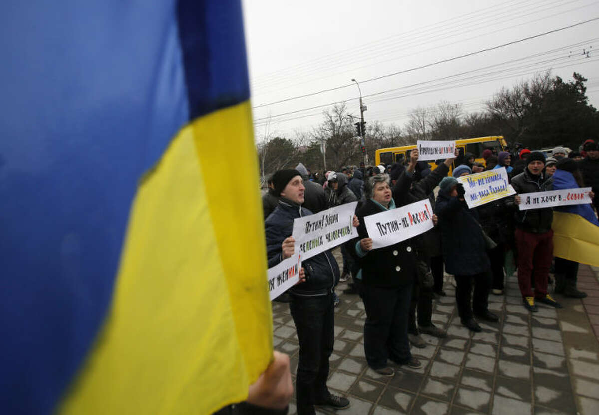 """People hold Ukrainian flags and banners that read: """"Putin! Take away the green men"""", """"They got me married without me being there"""", """"Referendum is a step to war"""", during a rally against the breakup of the country in Simferopol, Crimea, Ukraine, Tuesday, March 11, 2014. The Crimean parliament voted Tuesday that the Black Sea peninsula will declare itself an independent state if its residents agree to split off from Ukraine and join Russia in a referendum. Crimea's regional legislature on Tuesday adopted a """"declaration of independence of the Autonomous Republic of Crimea."""" The document specified that Crimea will become an independent state if its residents vote on Sunday in favor of joining Russia in the referendum. (AP Photo/Darko Vojinovic)"""