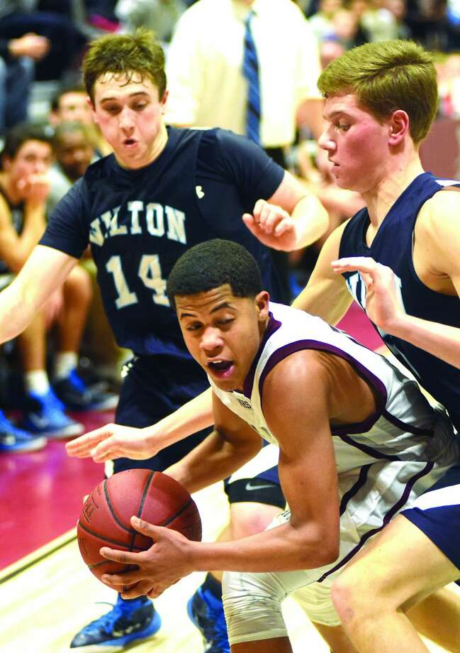 Naugatuck's Dayvon Russell, center, is trapped in a corner by Wilton's Scott Shouvlin, left, and Miles Elmasry during the fourth quarter of Thursday night's Class L state tournament second round game in Naugatuck. The host Greyhounds won the game, 62-54. (Hour photo/John Nash)