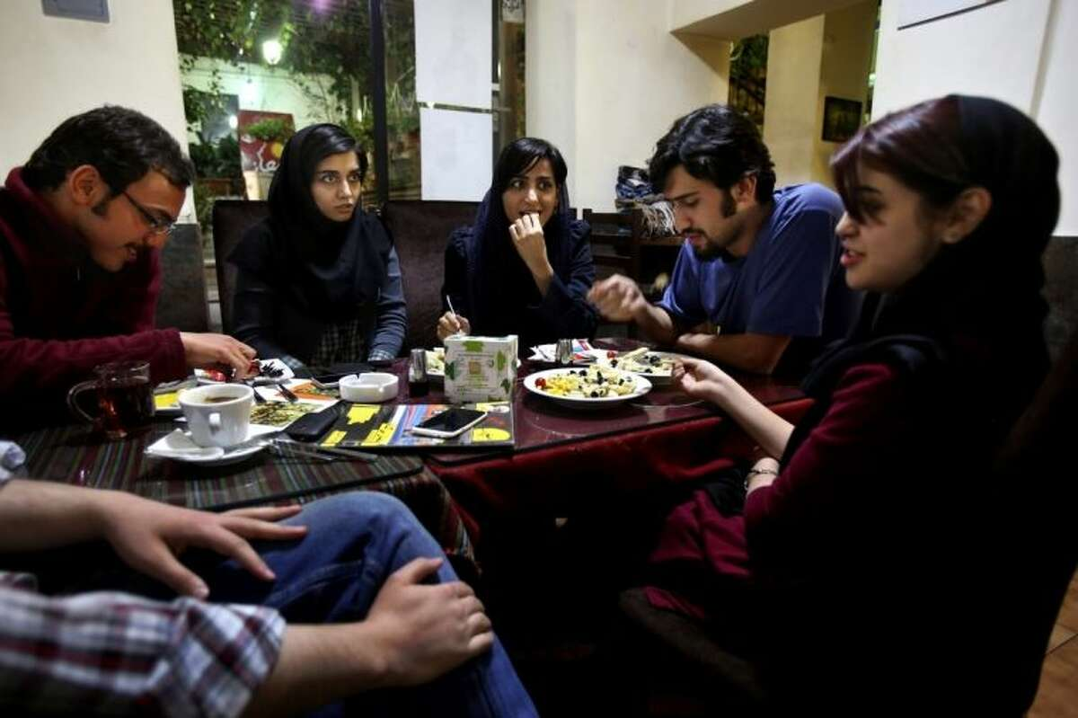 """In this Tuesday, March 4, 2014 photo, young Iranian adults meet at a cafe in Tehran, Iran. For years Iranian authorities kept the number of cafes limited since they were seen as a symbol of Western influence and places to spread non-Islamic beliefs. But reports of cafes being shut because they violate ?""""Islamic dignities?"""" have dropped markedly in recent months, suggesting a growing tolerance by the authorities. (AP Photo/Vahid Salemi)"""