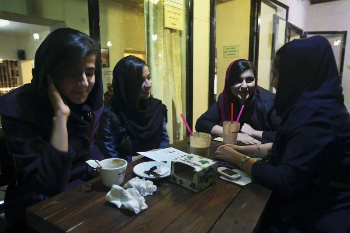In this Tuesday, March 4, 2014 photo, young Iranian ladies meet at a cafe in Tehran, Iran. The number of cafes started to increase in 2011, two years after the controversial re-election of former President Mahmoud Ahmadinejad that led to a massive crackdown on opposition activists. (AP Photo/Vahid Salemi)