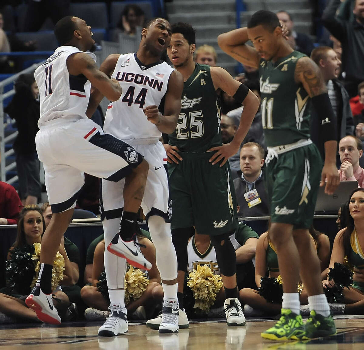 Connecticut's Ryan Boatright, left, and Rodney Purvis reacts as South Florida's Troy Holston Jr., center right, and Anthony Collins , right, look on during the first half of an NCAA college basketball game in the first round of the American Athletic Conference tournament, Thursday, March 12, 2015, in Hartford, Conn. (AP Photo/Jessica Hill)