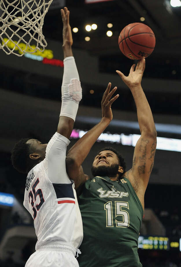 South Florida's Jaleel Cousins , right, shoots over Connecticut's Amida Brimah, left, during the first half of an NCAA college basketball game in the first round of the American Athletic Conference tournament, Thursday, March 12, 2015, in Hartford, Conn. (AP Photo/Jessica Hill)