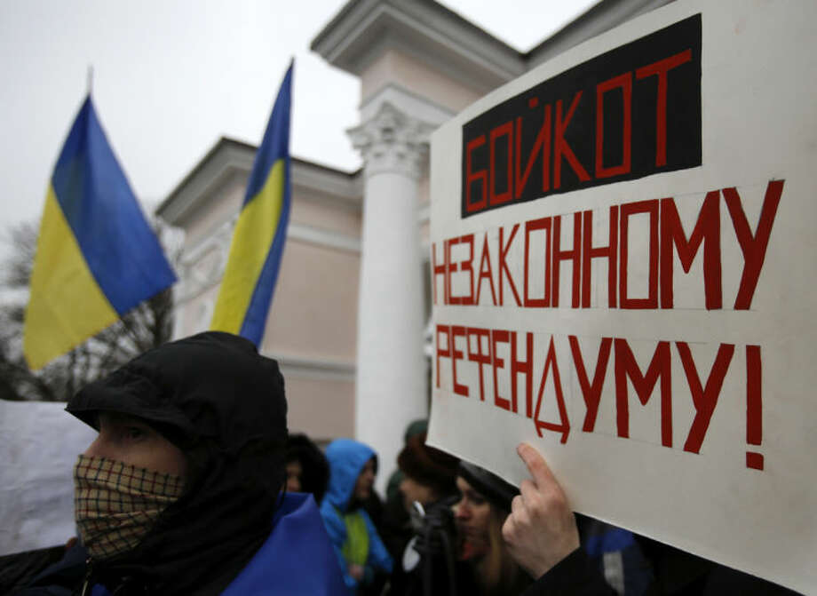 "A man holds a banner that reads: ""Boycott Illegal Referendum!"" during a rally against the breakup of the country Simferopol, Crimea, Ukraine, Tuesday, March 11, 2014. The Crimean parliament voted Tuesday that the Black Sea peninsula will declare itself an independent state if its residents agree to split off from Ukraine and join Russia in a referendum. Crimea's regional legislature on Tuesday adopted a ""declaration of independence of the Autonomous Republic of Crimea."" The document specified that Crimea will become an independent state if its residents vote on Sunday in favor of joining Russia in the referendum. (AP Photo/Darko Vojinovic)"