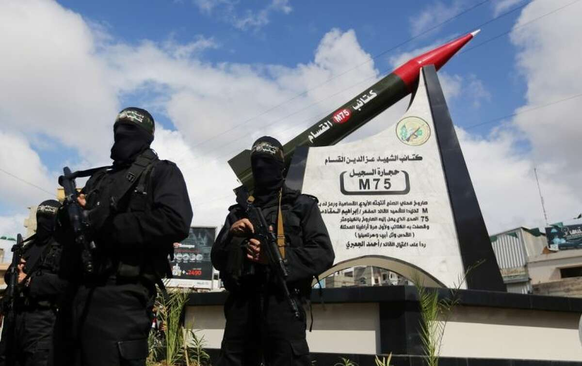 Hamas military wing members take part in a ceremony to inaugurate a monument marking the anniversary of the death of a senior Hamas official Ibrahim Maqadama, killed in an Israeli air strike in 2003, in Gaza City , Monday, March 10, 2014. The monument represents a model of the Hamas made longer-range M75 missile which has a range of about 80 kilometers and was used for the first time in 2012 against targets in Israel. (AP Photo/Hatem Moussa)