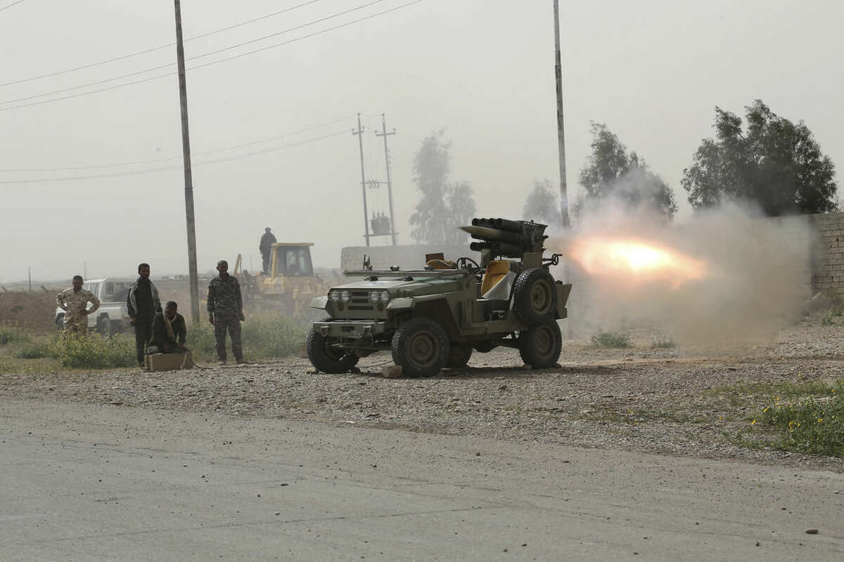 Members of an Iraqi Shiite militant group called Soldiers of Imam Ali Brigades launch rockets against Islamic State extremists positions in Tikrit, 80 miles (130 kilometers) north of Baghdad, Iraq, Friday, March 13, 2015. Iraqi forces entered Tikrit for the first time on Wednesday from the north and south. On Friday, they fought fierce battles to secure the northern Tikrit neighborhood of Qadisiyya and lobbed mortars and rockets into the city center, still in the hands of IS. (AP Photo/Khalid Mohammed)