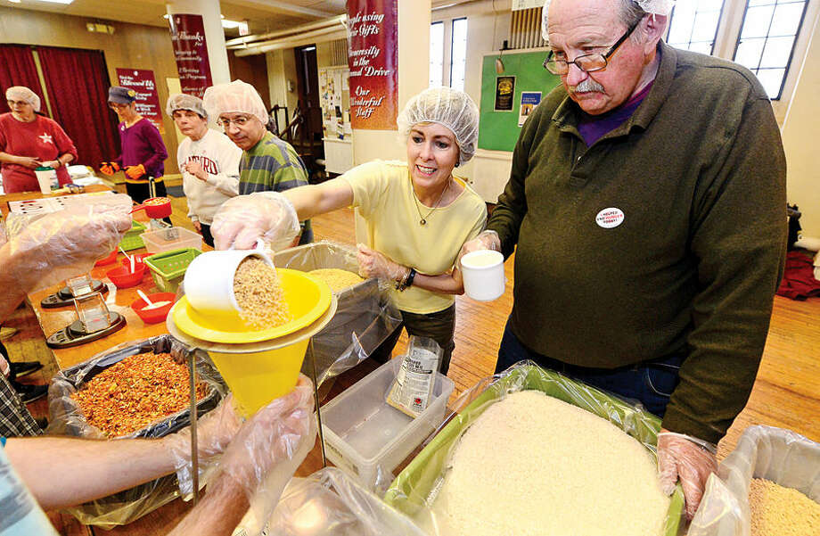 Hour photo / Erik Trautmann St. Paul's on the Green volunteers including Catherine Smith and Taber Hamilton help Stop Hunger Now with a sponsored meal packaging event at the church Saturday.