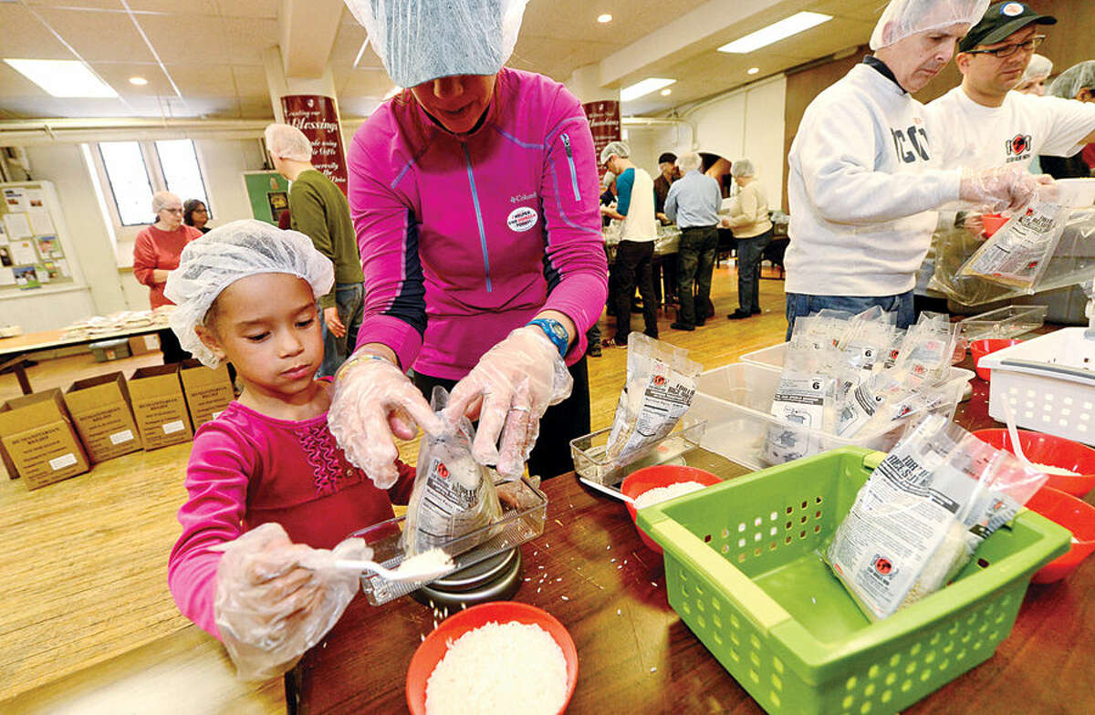 Hour photo / Erik Trautmann St. Paul's on the Green volunteers including Liliana Gomez, 6, and her mother, Margaret Gomez, help Stop Hunger Now with a sponsored meal packaging event at the church Saturday.