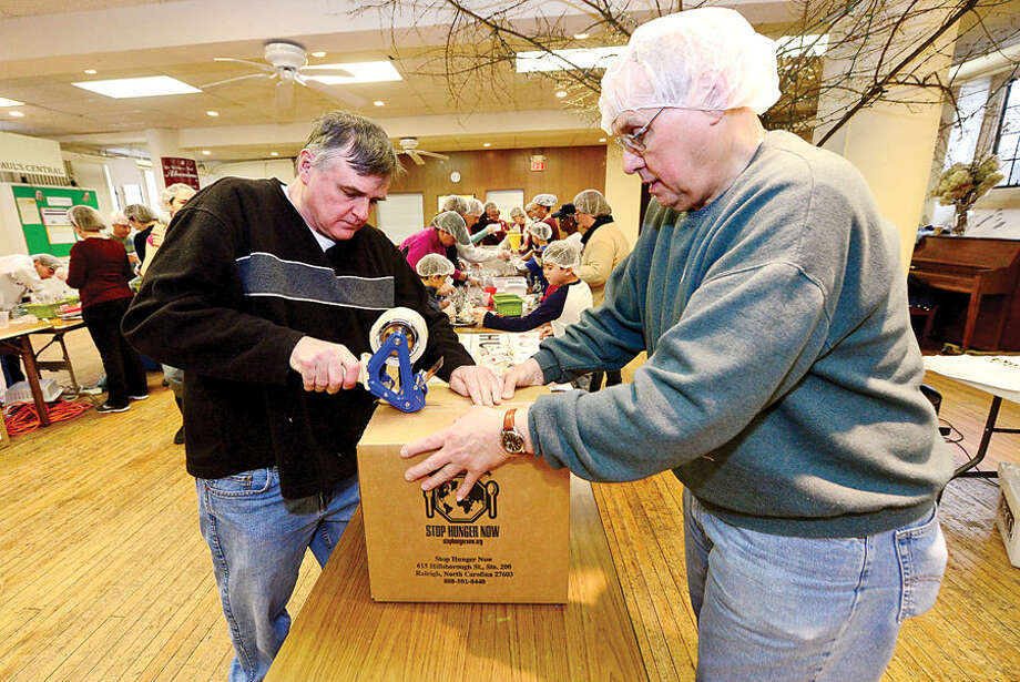 Hour photo / Erik Trautmann St. Paul's on the Green volunteers including Kurt Brown and Tom Schierloh help Stop Hunger Now with a sponsored meal packaging event at the church Saturday.