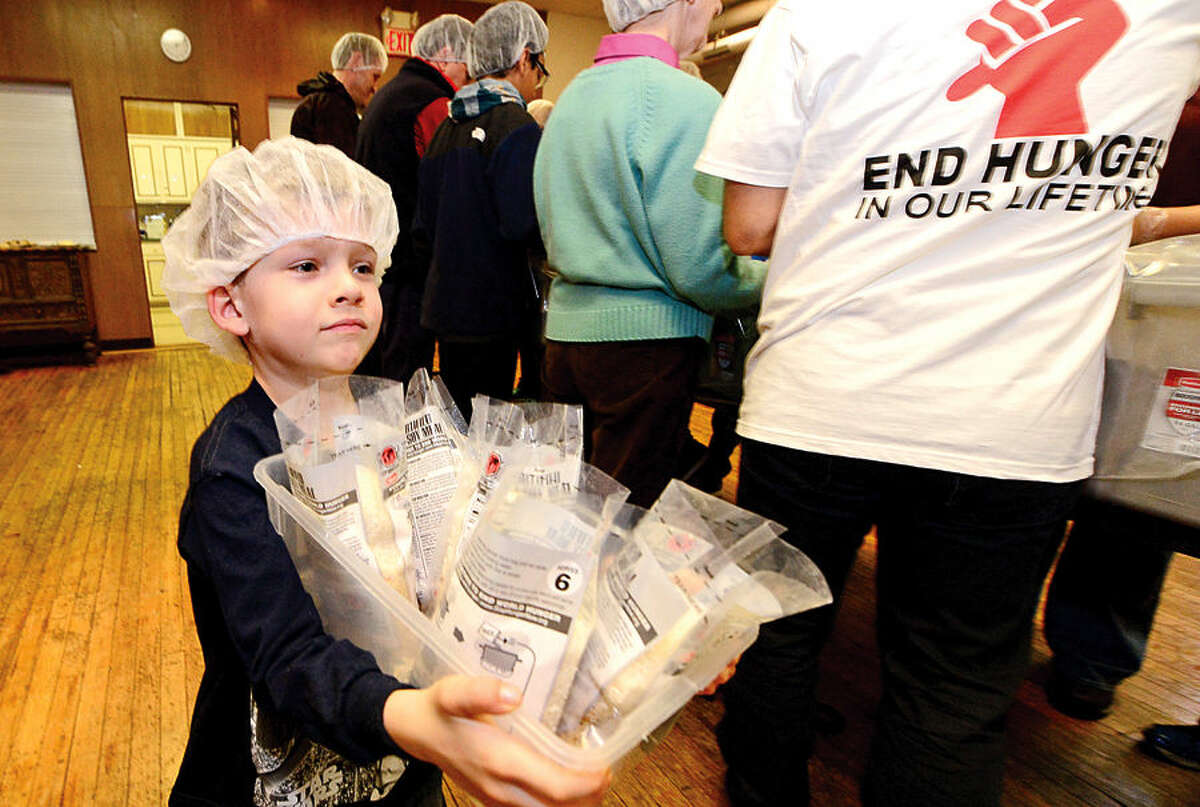 Hour photo / Erik Trautmann St. Paul's on the Green volunteers including Gavin Kopeski, 6, help Stop Hunger Now with a sponsored meal packaging event at the church Saturday.