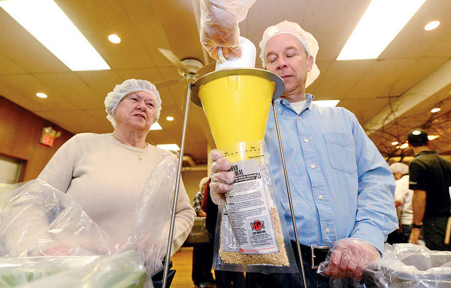 Hour photo / Erik Trautmann St. Paul's on the Green volunteers including Daine Drozd and George Anderson help Stop Hunger Now with a sponsored meal packaging event at the church Saturday.
