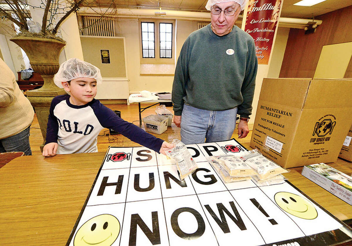 Hour photo / Erik Trautmann St. Paul's on the Green volunteers including 8 year old Kevin Hilton help Stop Hunger Now with a sponsored meal packaging event at the church Saturday.