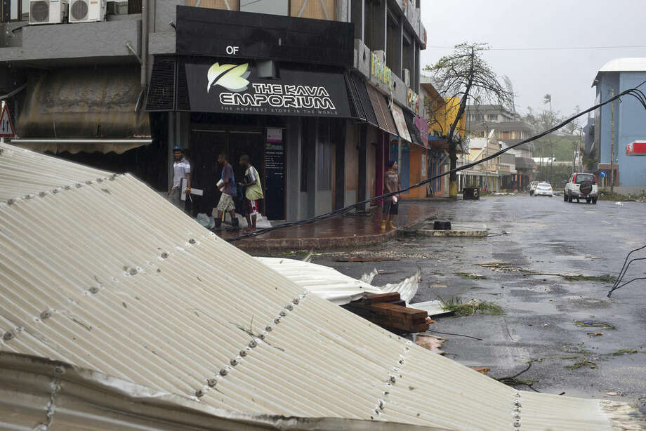 In this image provided by UNICEF Pacific, people walk past debris is scattered on a street in Port Vila, Vanuatu, Saturday, March 14, 2015, in the aftermath of Cyclone Pam. Winds from the extremely powerful cyclone that blew through the Pacific's Vanuatu archipelago are beginning to subside, revealing widespread destruction. (AP Photo/UNICEF Pacific, Humans of Vanuatu) EDITORIAL USE ONLY, NO SALES