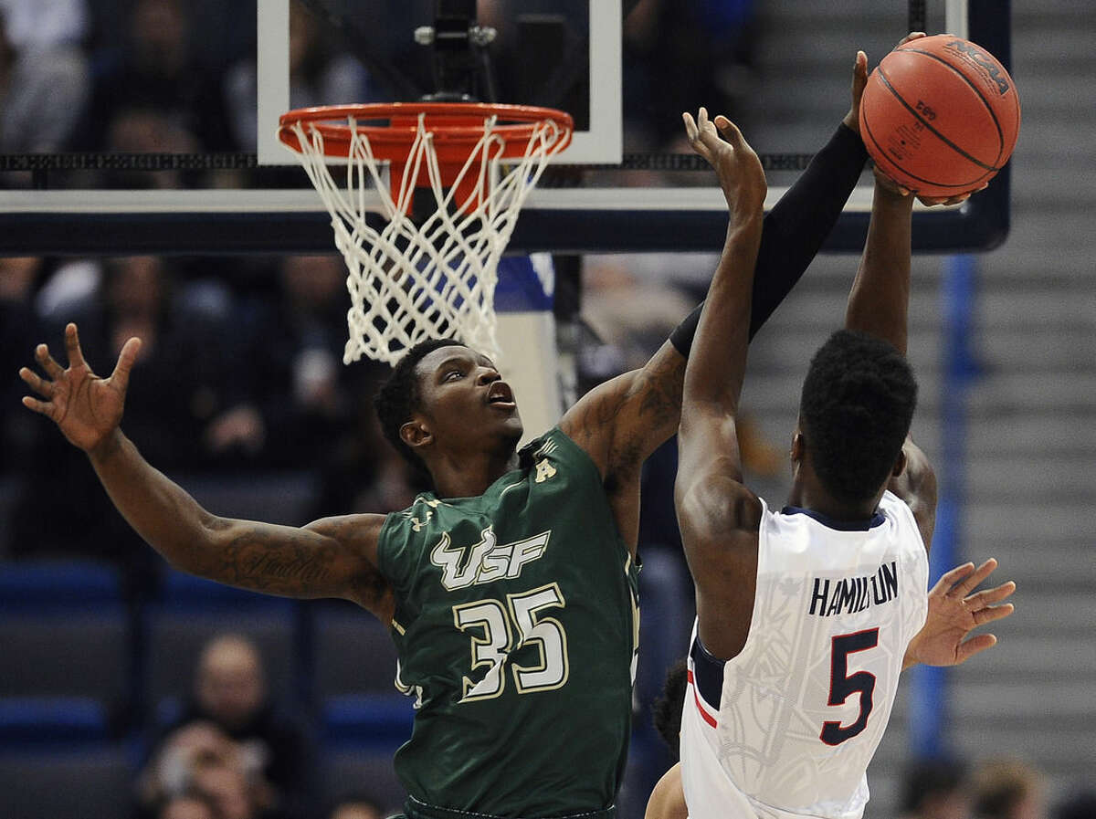 South Florida's Bo Zeigler, left, fouls Connecticut's Daniel Hamilton, right, during the first half of an NCAA college basketball game in the first round of the American Athletic Conference tournament, Thursday, March 12, 2015, in Hartford, Conn. (AP Photo/Jessica Hill)