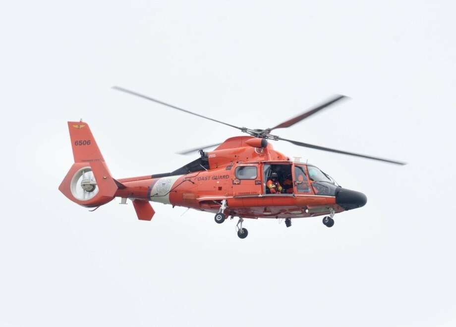 A U.S. Coast Guard helicopter flies over Santa Rosa Sound near Navarre, Fla., Wednesday, March 11, 2015. A fire official says divers are still trying to recover a flight recorder from the site of a helicopter crash that killed seven Marines and four soldiers. Mark Giuliano, the fire chief at Eglin Air Force Base, said Thursday that the Black Hawk helicopter was still in about 25 feet of water. (AP Photo/Northwest Florida Daily News, Devon Ravine)