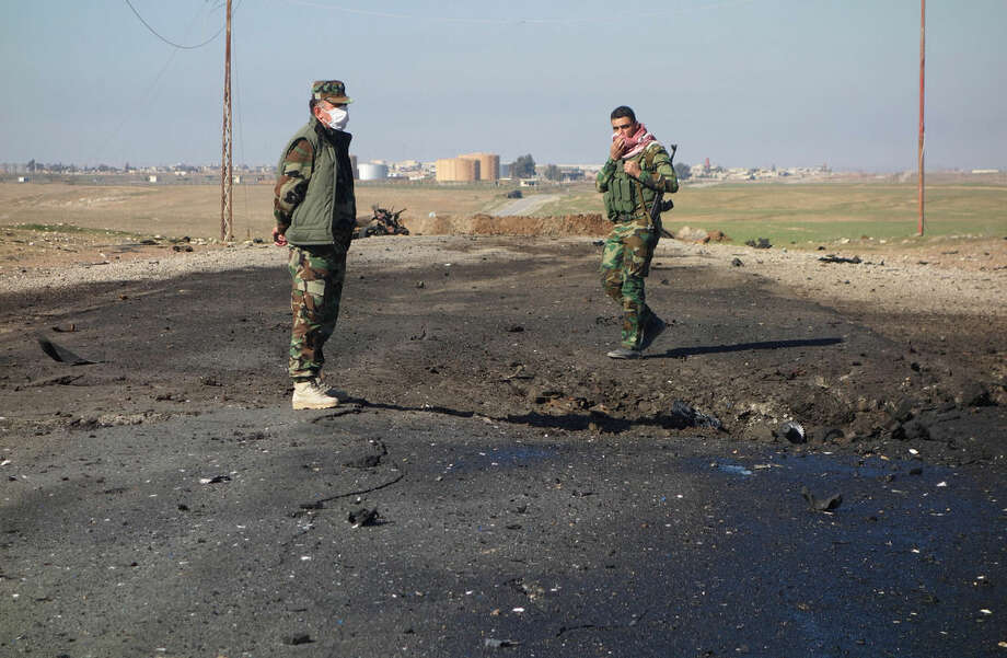 In this undated photo made avaialble Saturday, March 14, 2015, by the Kurdistan Region Security Council (KRSC), Kurdish soldiers survey the site of a bomb attack on a road between Mosul, Iraq, and the Syrian border in northern Iraq. Kurdish authorities in Iraq said Saturday they have evidence that the Islamic State group used chlorine gas as a chemical weapon against peshmerga fighters, the latest alleged atrocity carried out by the extremist organization now under attack in Tikrit. (AP Photo/Kurdistan Region Security Council)