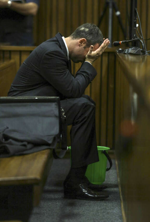 With a bucket on the floor nearby, Oscar Pistorius covers his face with his hands as he listens to cross questioning about the events surrounding the shooting death of his girlfriend Reeva Steenkamp, in court during his trial in Pretoria, South Africa, Tuesday, March 11, 2014. Pistorius is charged with the shooting death of Steenkamp, on Valentines Day in 2013. (AP Photo/Kevin Sutherland, Pool)
