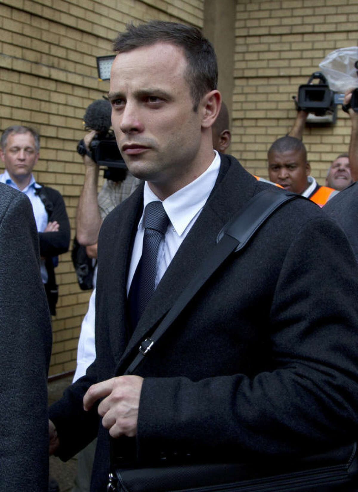 Oscar Pistorius, leaves the high court in Pretoria, South Africa, Tuesday, March 11, 2014. Pistorius is charged with murder for the shooting death of his girlfriend, Reeva Steenkamp, on Valentines Day in 2013. (AP Photo/Themba Hadebe)