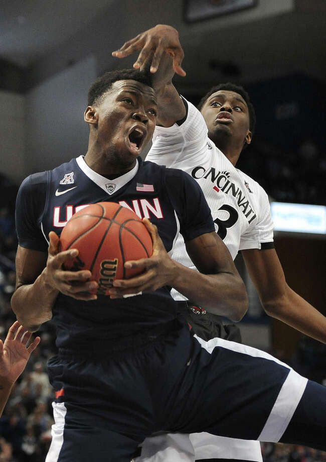 Cincinnati's Shaq Thomas, right, pressures Connecticut's Amida Brimah, left, during the second half of an NCAA college basketball game in the quarterfinal round of the American Athletic Conference tournament, Friday, March 13, 2015, in Hartford, Conn. (AP Photo/Jessica Hill)