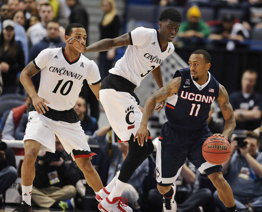 Connecticut's Ryan Boatright, right, dribbles as Cincinnati's Troy Caupain, left, and Shaq Thomas, center, defend during the first half of an NCAA college basketball game in the quarterfinals of the American Athletic Conference tournament, Friday, March 13, 2015, in Hartford, Conn. (AP Photo/Jessica Hill)