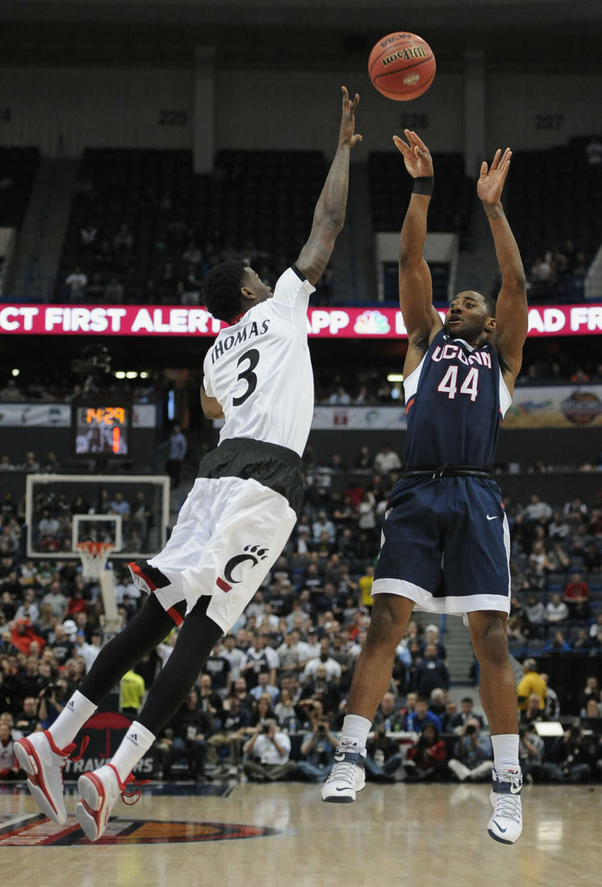 Connecticut's Rodney Purvis, right, shoots over Cincinnati's Shaq Thomas during the second half of an NCAA college basketball game in the quarterfinals of the American Athletic Conference tournament, Friday, March 13, 2015, in Hartford, Conn. (AP Photo/Jessica Hill)