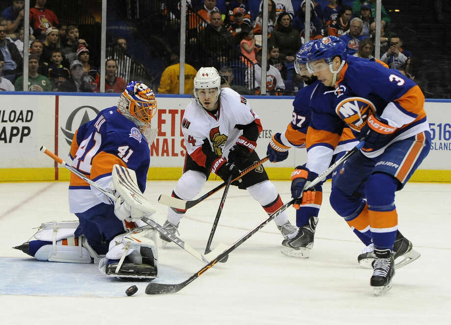 New York Islanders goalie Jaroslav Halak (41), defenseman Travis Hamonic (3) and defenseman Brian Strait (37) defend against Ottawa Senators center Jean-Gabriel Pageau (44) in the first period of an NHL hockey game on Friday, March 13, 2015, in Uniondale, N.Y. (AP Photo/Kathy Kmonicek)