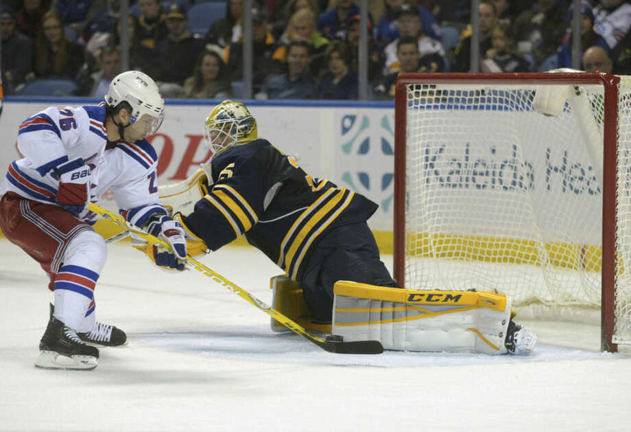 New York Rangers right winger Martin St. Louis, left, backhands the puck as Buffalo Sabres goaltender Anders Lindback (35), of Sweden, makes a pad save during the second period of an NHL hockey game Saturday, March 14, 2015, in Buffalo, N.Y. (AP Photo/Gary Wiepert)