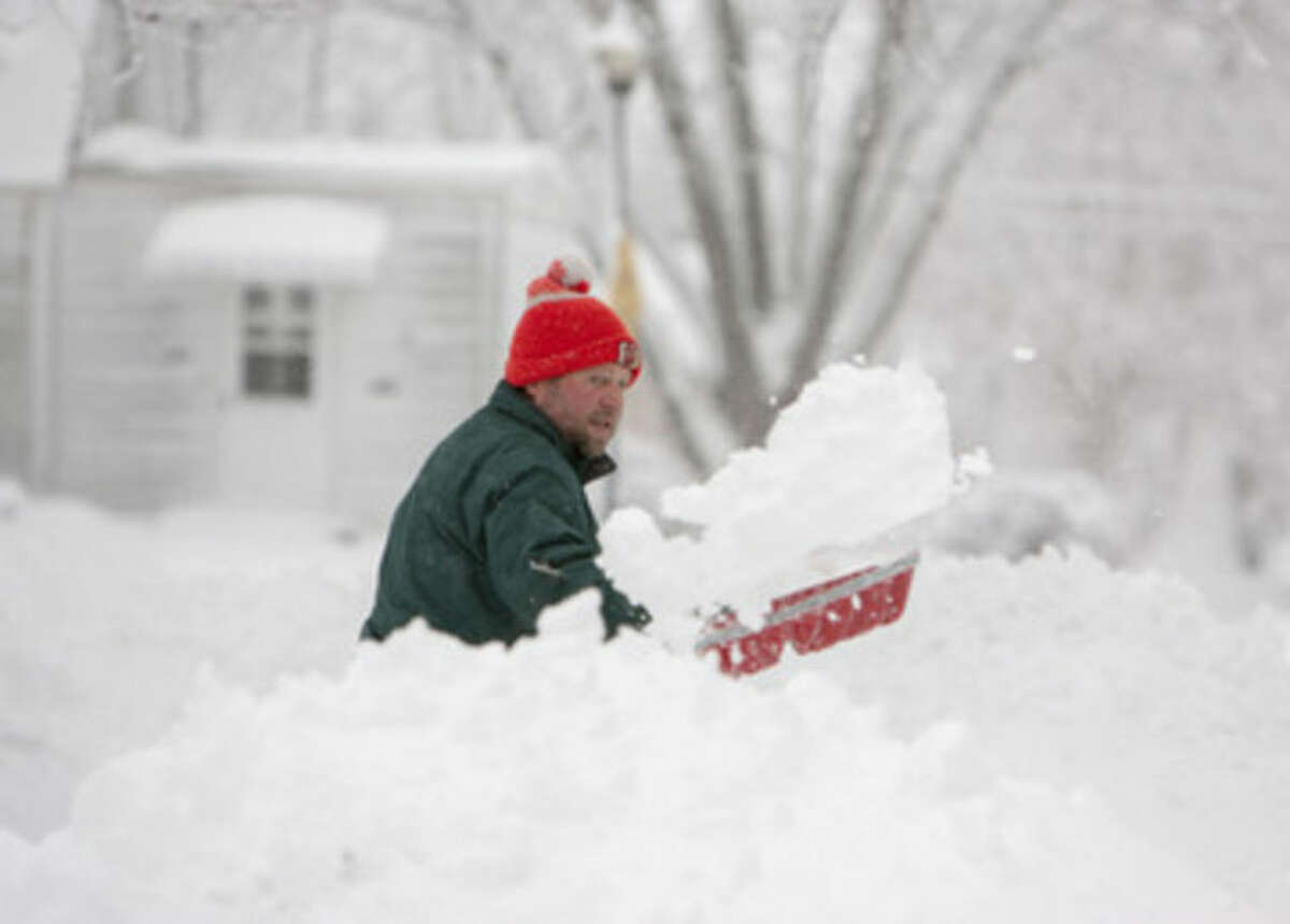 Chris Nix shovels out for the piles of snow in his driveway at the corner of Hoagland and West Maplegrove avenues, Fort Wayne, Ind. More than five inches of new snow fell on the area Wednesday morning, March 12, 2014. (AP Photo/ The Journal Gazette, Chad Ryan)