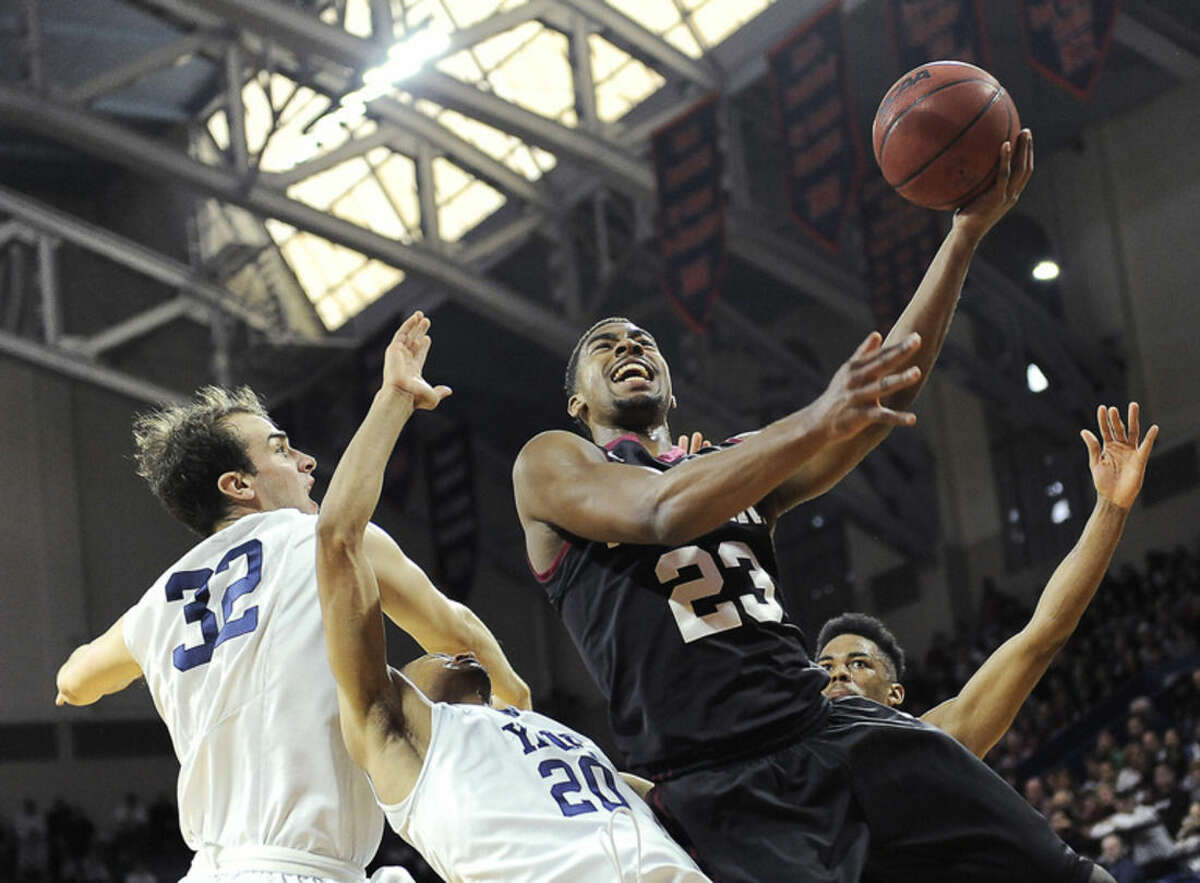 Harvard's Wesley Saunders (23) drives to the basket and shoots over Yale's Javier Duren (20) and Greg Kelley (32) during the first half of an NCAA college basketball Ivy League playoff game on Saturday, March 14, 2015, in Philadelphia. (AP Photo/Michael Perez)