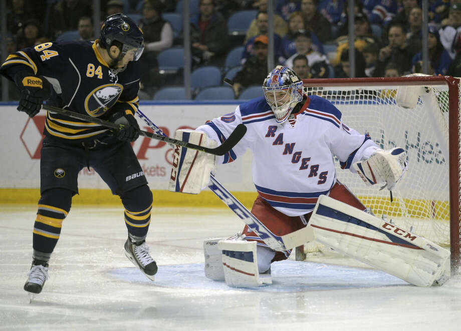 Buffalo Sabres center Phillip Varone (84) deflects the puck over the shoulder of New York Rangers goaltender Mackenzie Skapski during the first period of an NHL hockey game Saturday, Mar. 14, 2015, in Buffalo, N.Y. (AP Photo/Gary Wiepert)
