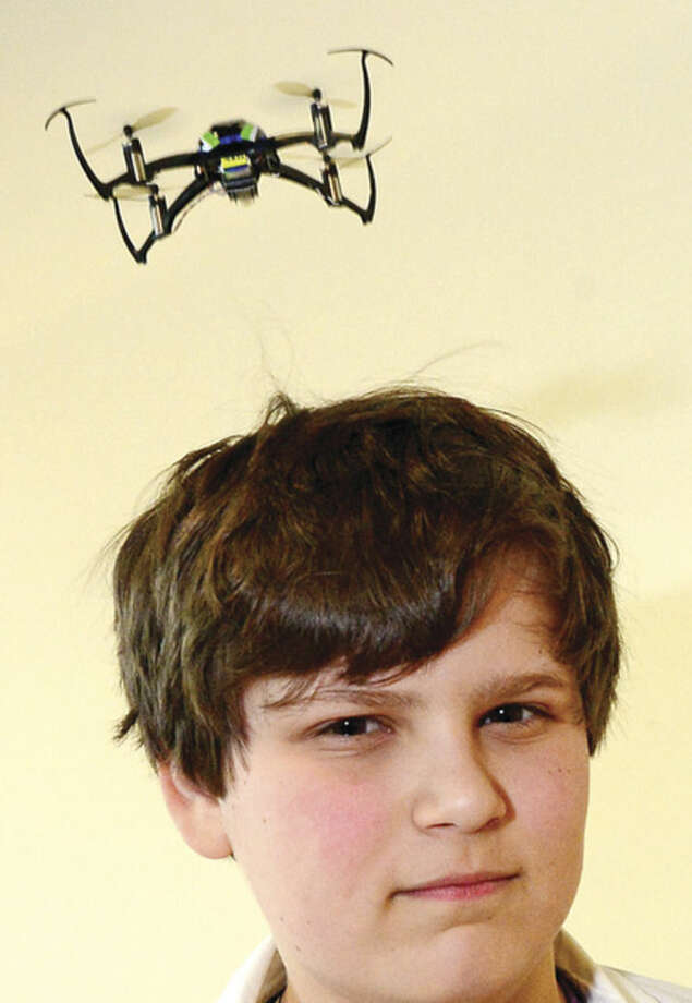 Hour photo / Erik Trautmann Evan Kryger, 11, launches a quad copter off his head as the Fairfield County Makers' Guild celebrates its one-year anniversary with a open house Saturday.