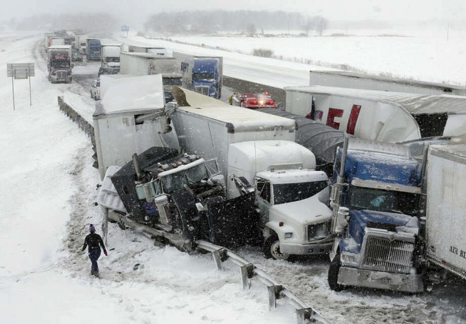 A multi-vehicle accident in the eastbound lane of the Ohio Turnpike near the County Road 268 overpass ties up traffic Wednesday, March 12, 2014, near Clyde, Ohio. Pileups on the Ohio Turnpike involving at least 50 vehicles killed at least two people and seriously injured a state trooper on Wednesday, said the Ohio State Highway Patrol. (AP Photo/The Toledo Blade, Jeremy Wadsworth)