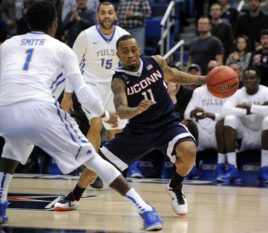 Connecticut's Ryan Boatright (11) drives past Tulsa's Rashad Smith during the first half of an NCAA college basketball game in the semifinals of the American Athletic Conference tournament in Hartford, Conn., on Saturday, March 14, 2015. (AP Photo/Fred Beckham)