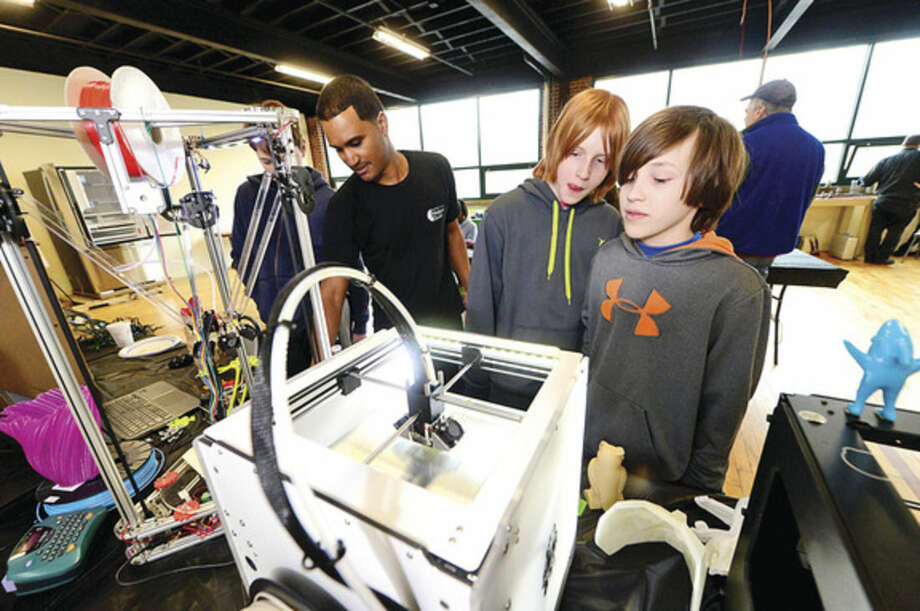 Hour photo / Erik Trautmann Ethen Knox and Evan Lansing look over the Ultimaker 2 3D printer as the Fairfield County Makers' Guild celebrates its one-year anniversary with a open house Saturday.