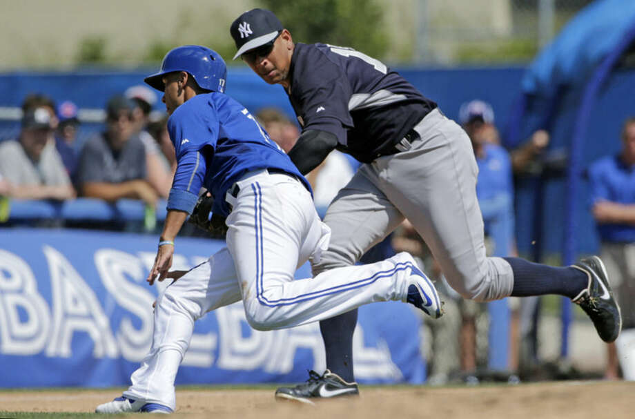 New York Yankees third baseman Alex Rodriguez, right, tries to tag out Toronto Blue Jays Ryan Goins (17) but misses him when Blue Jays' Devon Travis hit into a sixth-inning fielder's choice in a spring training baseball game in Dunedin,Fla., Saturday, March 14, 2015. The Blue Jays defeated the Yankees 1-0. (AP Photo/Kathy Willens)