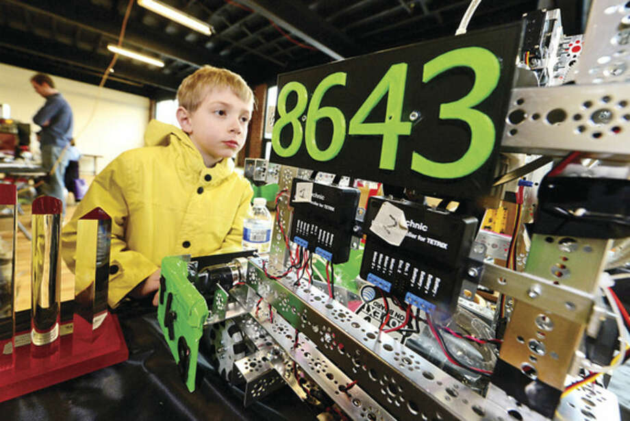 Hour photo / Erik Trautmann 6-year-old Bradford Benton looks over a robot built by the Techno Geeks team as the Fairfield County Makers' Guild celebrates its one-year anniversary with a open house Saturday.
