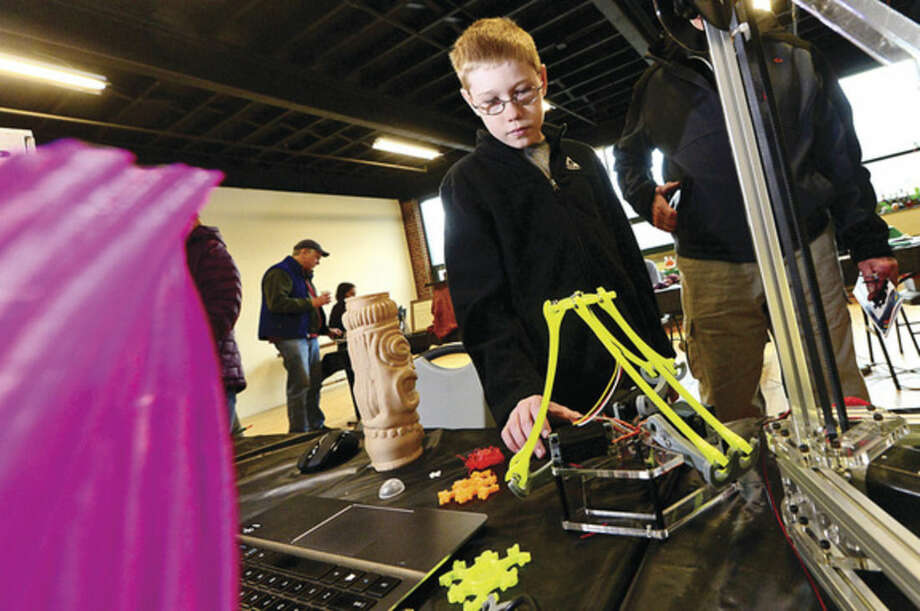 Hour photo / Erik Trautmann Jack Spahr looks over some 3D printers as the Fairfield County Makers' Guild celebrates its one-year anniversary with a open house Saturday.