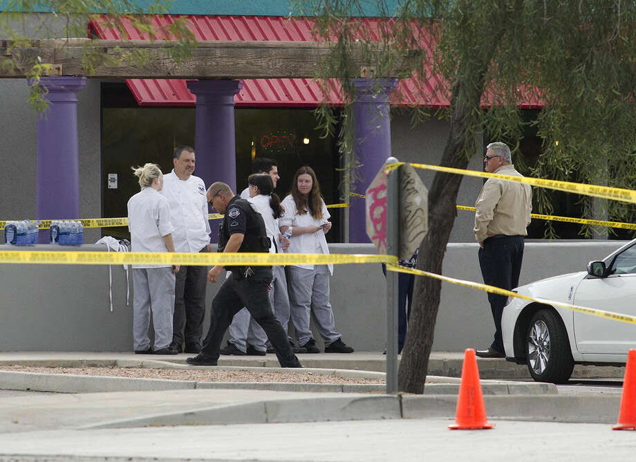 Mesa police talk to eyewitness at the scene of a shooting, Wednesday, March 18, 2015 in Mesa, Ariz. A gunman wounded at least four people across multiple locations in the Phoenix suburb and police warned residents to stay indoors as they hunt for the suspect. (AP Photo/The Arizona Republic, Nick Oza) MARICOPA COUNTY OUT; MAGS OUT; NO SALES
