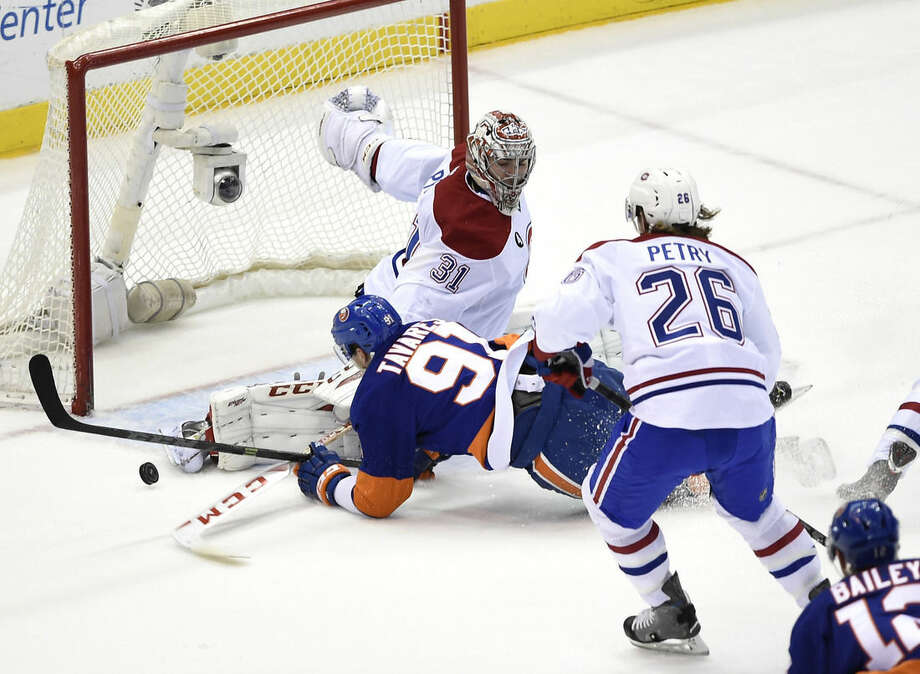 Montreal Canadiens goalie Carey Price (31) blocks a shot on goal by New York Islanders center John Tavares (91) as Canadiens defenseman Jeff Petry (26) defends in the first period of an NHL hockey game on Saturday, March 14, 2015, in Uniondale, N.Y. (AP Photo/Kathy Kmonicek)